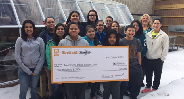 Students pose with giant check